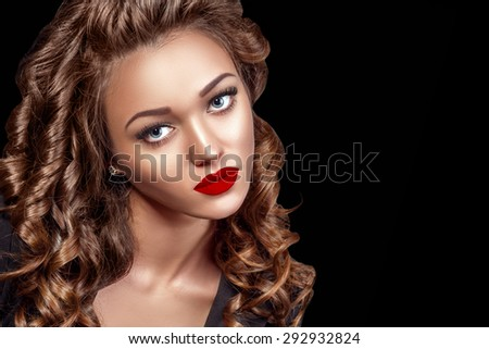 Beautiful Woman Model with Curls, Red Matte lips. Beauty face closeup. Isolated on Black Background. Long Shiny Curly Hair. Hairstyle.  - stock photo