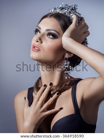 Beautiful woman model with professional makeup, in jewelry. Golden crown - stock photo