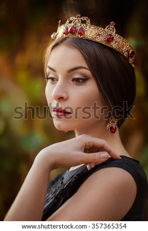 Beautiful woman model with professional makeup, in jewelry. Golden crown in style D&G