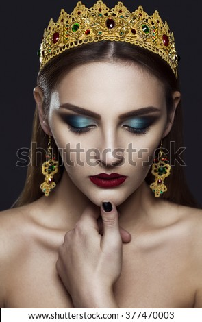 Beautiful woman model with professional makeup, in jewelry. Golden Crown. Red lipstick.