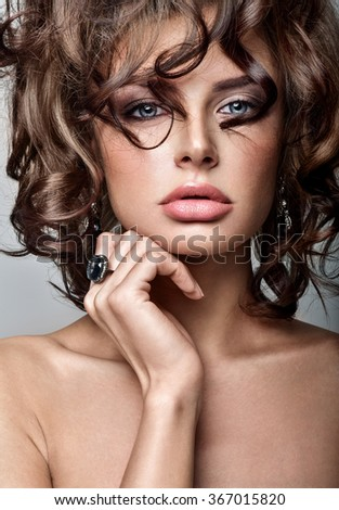 Beautiful woman model with professional makeup, in jewelry. Luxury curly hair. - stock photo