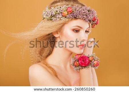 Beautiful woman model with wreath of bright flowers on her head. On yellow background - stock photo