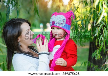 Beautiful woman mom with a child walks in the park in summer. - stock photo