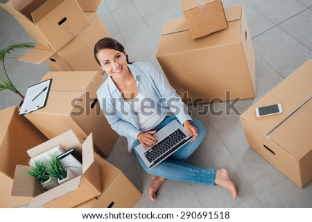 Beautiful woman moving in her new house and unpacking, she is sitting on the floor surrounded by boxes, using a laptop and smiling at camera