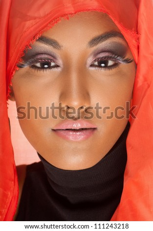 beautiful woman of east indian descent looks straight at you under an orange hood - stock photo