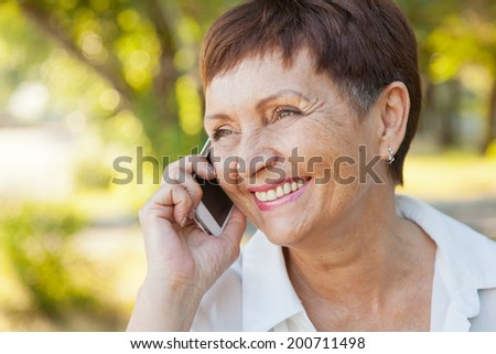 beautiful woman of 50 years with a mobile phone outdoors - stock photo
