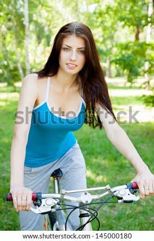 beautiful woman on a bicycle in the park - stock photo