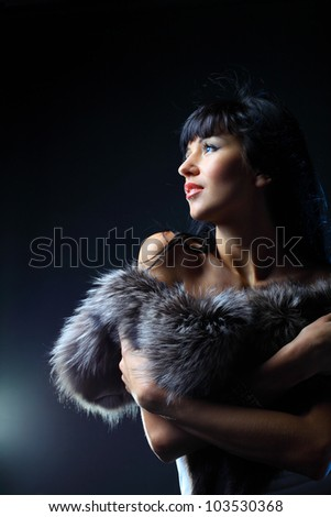 Beautiful woman on a dark background looking at copyspace - stock photo
