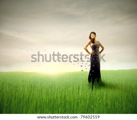 Beautiful woman on a green meadow with butterflies flying from her dress - stock photo