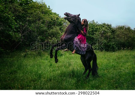 Beautiful woman on a horse dressed in long violet dress