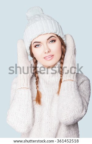 Beautiful woman on a light background. A brunette woman in warm clothes. Attractive young woman on a background of mint in a cap and a sweater. Woman in the winter, the studio BLUE gentle background.