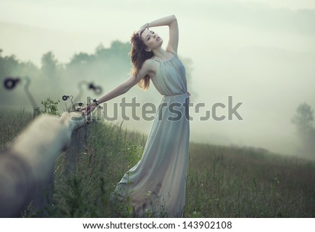 Beautiful woman on a morning meadow - stock photo