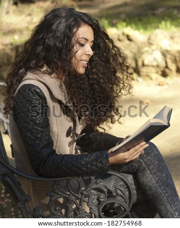 Beautiful woman on a park bench reading a book in autumn
