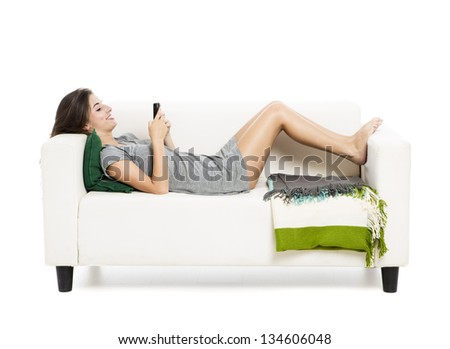 Beautiful woman on a sofa drinking tea, isolated over a white background - stock photo