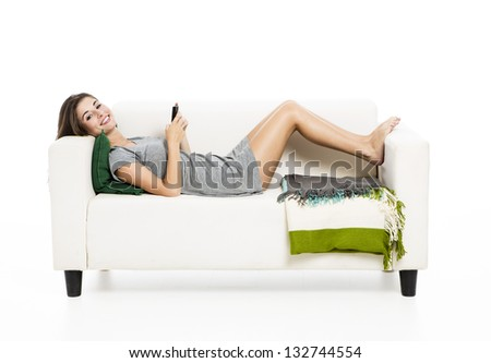 Beautiful woman on a sofa with a cellphone texting, isolated in white - stock photo