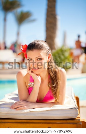 beautiful woman on a tropical beach on a  sun lounger - stock photo