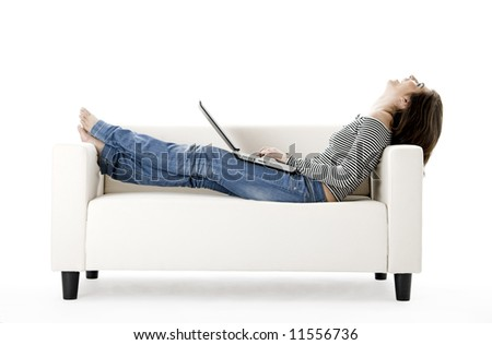 Beautiful woman on a white sofa with a laptop - stock photo