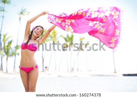 Beautiful woman on beach waving pink scarf in happy bliss on travel vacation. Graceful pretty mixed race young woman in pink bikini on hawaiian beach with palm trees. Big Island, Hawaii, United States - stock photo