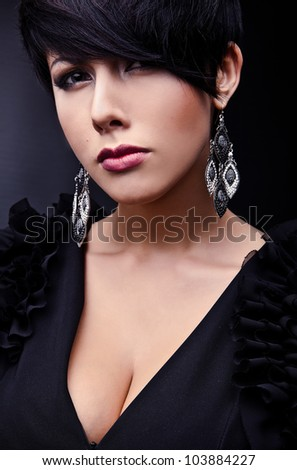 Beautiful woman on black classical dress pose in studio.