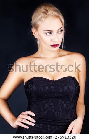Beautiful woman on black classical dress pose in studio - stock photo