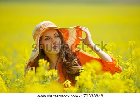 beautiful woman on blooming rapeseed field in summer - stock photo