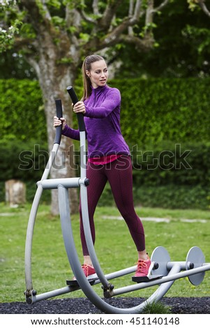 Beautiful woman on cross trainer in park