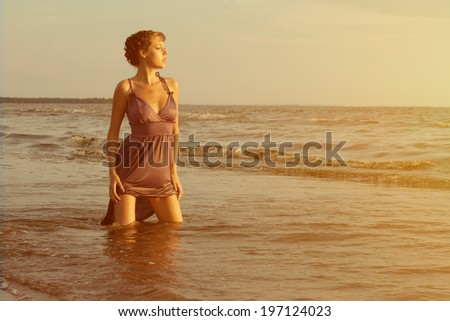 Beautiful woman on the beach at sunset.