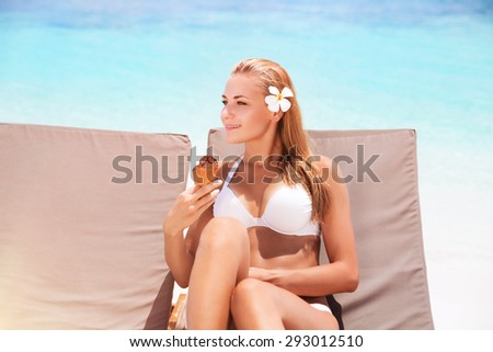 Beautiful woman on the beach, pretty girl sitting on sunbed with two ice cream in hand waiting for her boyfriend, female enjoying summer vacation on tropical resort - stock photo