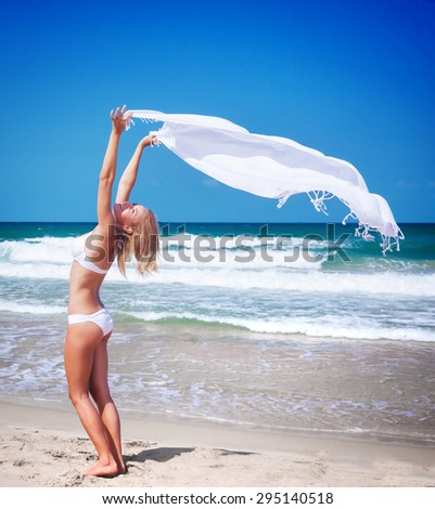 Beautiful woman on the beach, sexy slim model with raised up hands holding white scarf fluttering in the wind, happy summer vacation - stock photo
