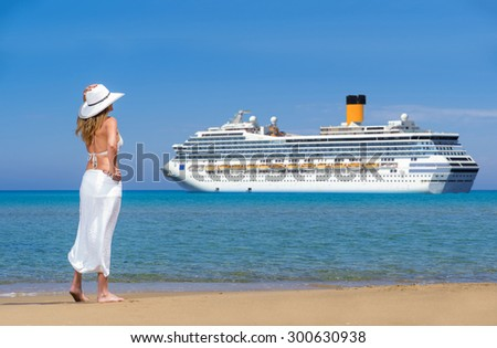 Beautiful woman on the beach watching a cruise ship passing by - stock photo