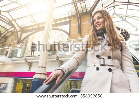 Beautiful woman on the escalator at train station, going down and looking away from camera. Concepts of travel and lifestyle, during autumn or winter season. - stock photo