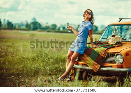 Beautiful woman on the picnic is drinking wine near a car. - stock photo