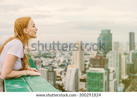 Beautiful Woman on the Roof Top of Big Tourist City in Travel - stock photo