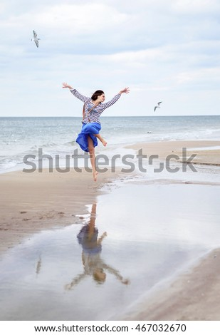 Beautiful woman on the sand. Happy young girl flying with seagulls on the sea. Portrait of a barefoot woman on the beach. Autumn.