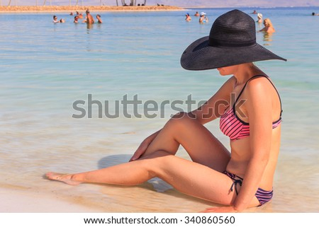 Beautiful woman on the shore of the Dead Sea - stock photo