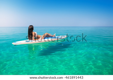 Beautiful woman on the Standup paddlbording relaxing in the sea with clean water. Leisure activities in the tropical ocean islands on surf.
