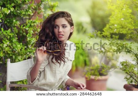 Beautiful woman on the terrace of an Italian country garden - stock photo