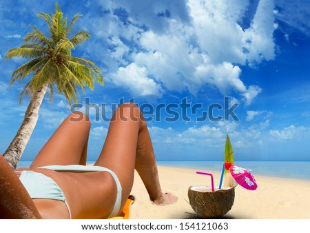Beautiful woman on the tropical beach with coconut cocktail