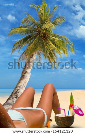 Beautiful woman on the tropical beach with coconut cocktail - stock photo