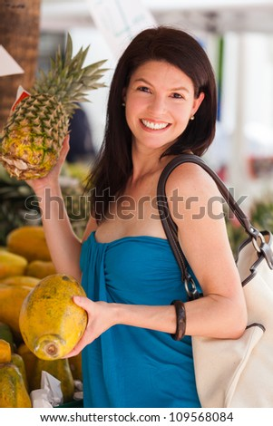 Beautiful woman outdoor lifestyle portrait in a fruit market. - stock photo