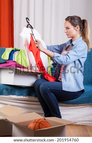 Beautiful woman packing her clothes to boxes because of moving house