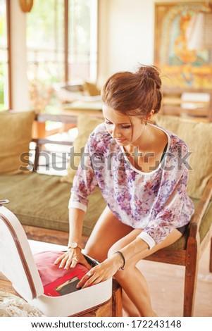 beautiful woman packing luggage - stock photo
