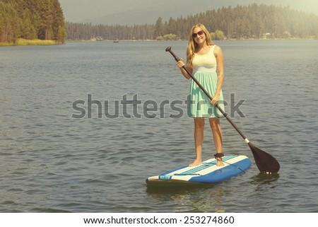 Beautiful woman paddleboarding on scenic lake - stock photo