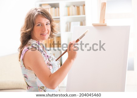 Beautiful woman painting on canvas at her home or workshop - stock photo