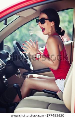 Beautiful woman panic in the red car  - stock photo