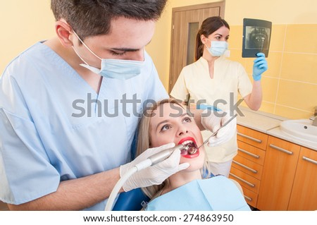Beautiful woman patient in dentist office or cabinet getting her teeth checked by the young doctor - stock photo