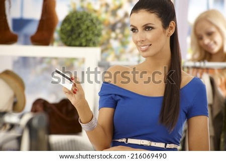 Beautiful woman paying by credit card at clothes store, smiling. - stock photo