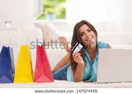 Beautiful woman paying by credit card for shopping at home  - stock photo