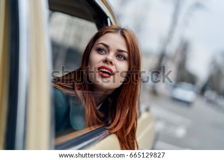 Beautiful woman peeking out of car window, woman sitting in car.