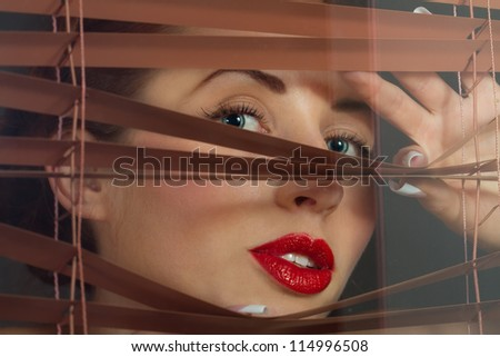 beautiful woman peering through blinds - stock photo
